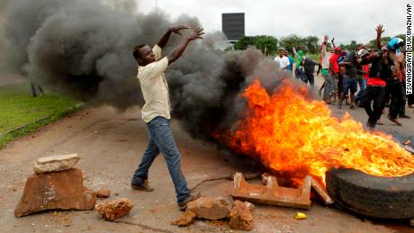 Protesters gather near a burning tire during a demonstration over the hike in fuel prices in Harare, Zimbabwe, on  January 15.