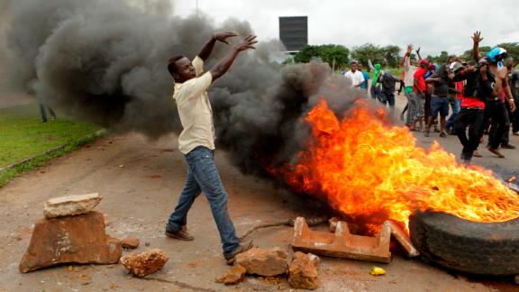 Protestors gather near a burning tire during a demonstration over the hike in fuel prices in Harare, Zimbabwe, Tuesday, Jan. 15, 2019.  A Zimbabwean military helicopter on Tuesday fired tear gas at demonstrators blocking a road and burning tires in the capital on a second day of deadly protests after the government more than doubled the price of fuel in the economically shattered country. (AP Photo/Tsvangirayi Mukwazhi)