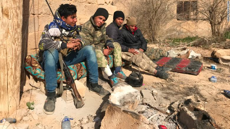 Syrian Democratic Forces (SDF) troops take a break between the town of Sha'fa and Soussa, one of the last ISIS-controlled villages in southeast Syria.