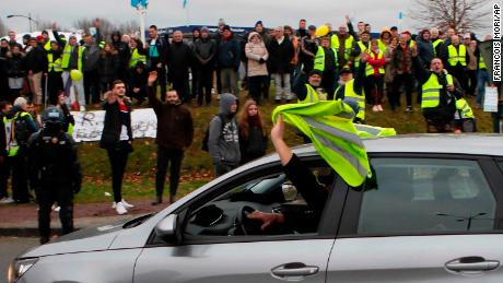 A car driver shows his yellow vest to cheer protesters as French President Emmanuel Macron visits Normandy on Tuesday.