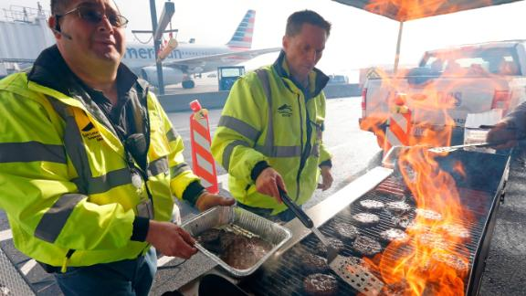 Airport operation workers flip burgers and hot dogs at Salt Lake City International Airport on January 16. They treated federal workers to a free lunch.