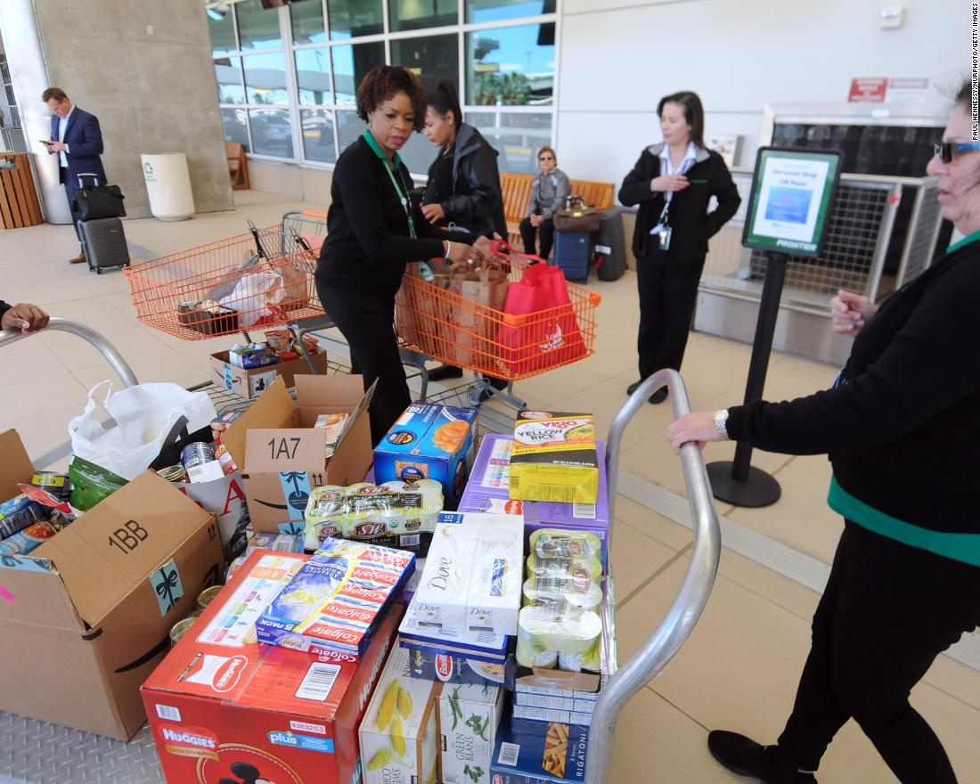 Employees of Frontier Airlines bring donated food for federal workers to Orlando International Airport on Wednesday, January 16.