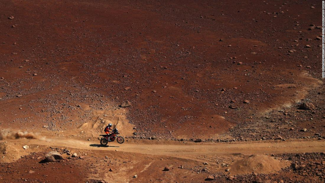 A red landscape acts as the backdrop as KTM rider Luciano Benavides tackles stage seven of the event.
