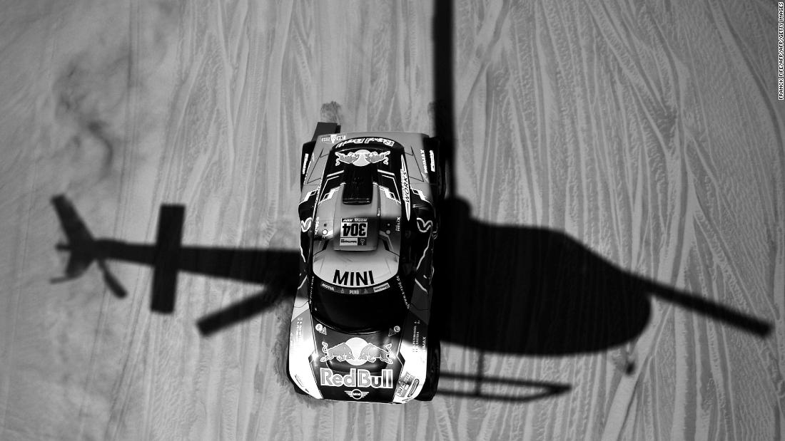 A helicopter casts is shadow over Mini driver Stephane Peterhansel and co-driver David Castera.