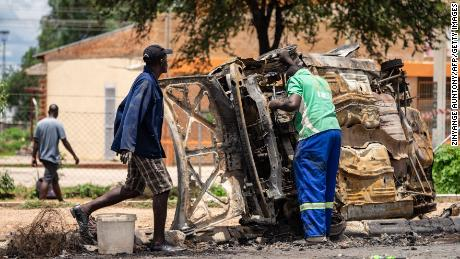 A scrap metal collector salvages sellable parts from a car burned during the protests in Bulawayo on January 17.