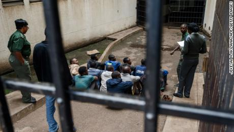 Prison guards watch over men arrested during the protests as they wait for their hearing at the Law Court in Harare on January 16.