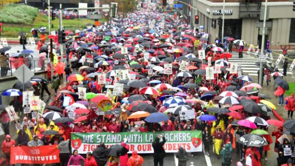 Thousands of teachers marched in the rain demanding more school staffing and higher salaries.