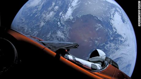 A dummy in a space suit can be seen behind the wheel of the red Tesla sports car by Elon Musk hovering in space.