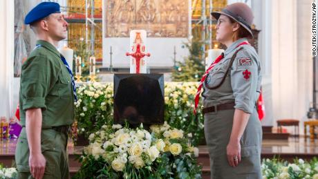 Boy and girl scouts stand at attention by the urn with ashes of slain Gdansk city Mayor Pawel Adamowicz during his funeral Mass.