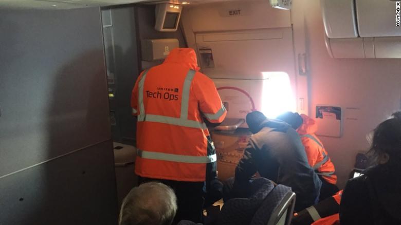 Passenger Steven Lau posted this photo of United workers trying to fix an emergency exit door.