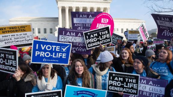 """Pro-choice activists hold signs in response to anti-abortion activists participating in the """"March for Life,"""" an annual event to mark the anniversary of the 1973 Supreme Court case Roe v. Wade, which legalized abortion in the US, outside the US Supreme Court in Washington, DC, January 18, 2019."""