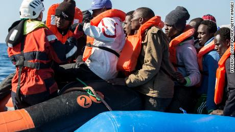 A group of 47 migrants is helped by a Sea Watch 3 crew member (left) during a rescue operation off Libya in January 2019.