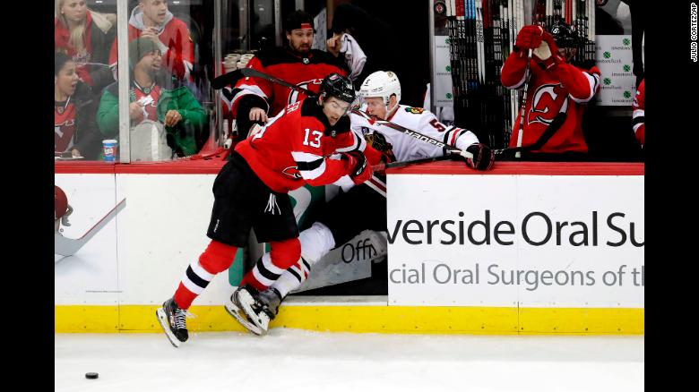 Chicago Blackhawks defenseman Connor Murphy gets checked into the New Jersey Devils bench by center Nico Hischier during the third period of an NHL hockey game on January 14 in Newark, New Jersey.