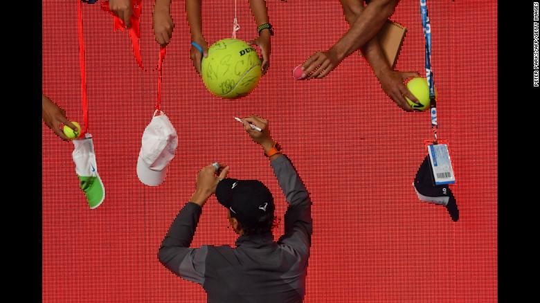 Tennis star Rafael Nadal signs autographs after his victory over Matthew Ebden during their men's singles match on the third day of the Australian Open on Wednesday, January 16.