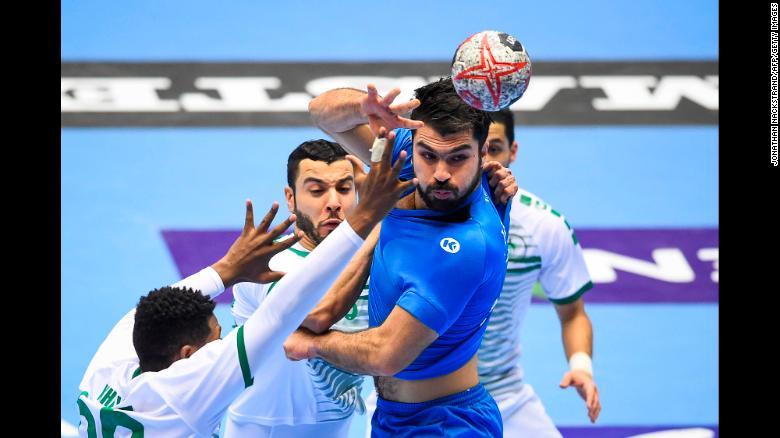 Tunisia's Oussama Jaziri competes with three Saudi Arabia players during an IHF Men's World Championship handball match on Tuesday, January 15.