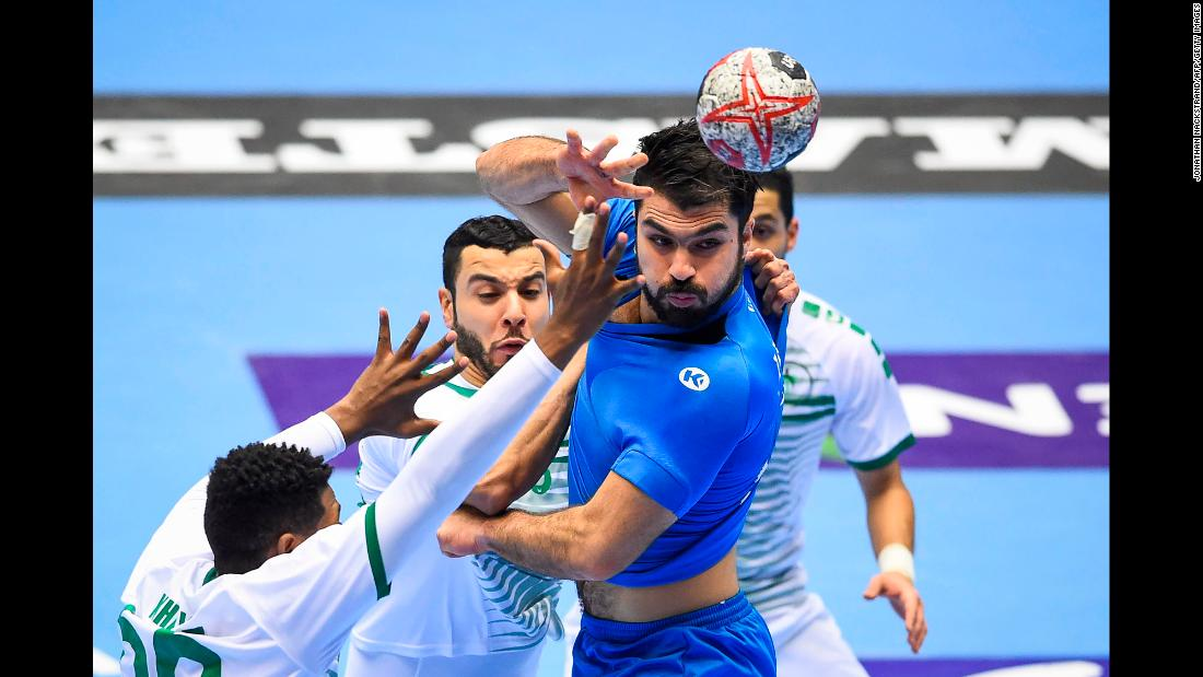 Tunisia's Oussama Jaziri competes with three Saudi Arabia players during an IHF Men's World Championship handball match on Tuesday, January 15.