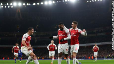 Arsenal's French striker Alexandre Lacazette celebrates scoring his team's first goal with teammates Granit Xhaka and Aaron Ramsey.