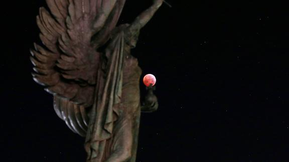 The blood moon with a statue in Brighton, England.