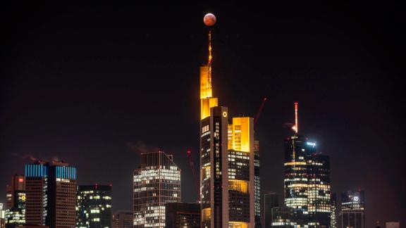 "As a red, so-called ""blood moon"", the full moon stands above the Frankfurt skyscrapers and the Commerbank (M) headquarters, while it steps into the shadow of the earth."