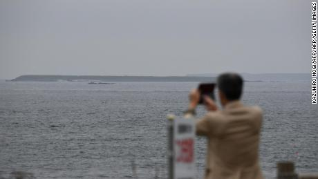 A tourist takes pictures of an islet making up part of the Habomai Islands at Cape Nosappu, a point on the Nemuro peninsula, Hokkaido prefecture.