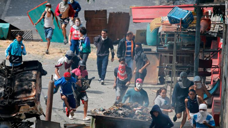 Anti-government protesters in the Cotiza neighborhood of Caracas clash with security forces as they show support for an apparent mutiny by a group of soldiers.