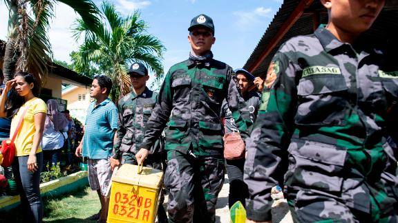 A policeman carries a ballot box at a voting precinct in Cotabato on the southern Philippine island of Mindanao on January 21, 2019, during a vote on giving the nation's Muslim minority greater control over the region.