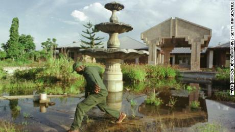 A soldier steps across an overgrown fountain in front of one of the late Mobutu Sesse Seko's palaces September 15, 2000 in Gbadolite, Congo. All three of the elaborate palaces in Gbadolite have long been looted.