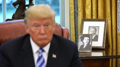 Framed photos of President Donald Trump's parents, Fred and Mary, sit on a table in the Oval Office.