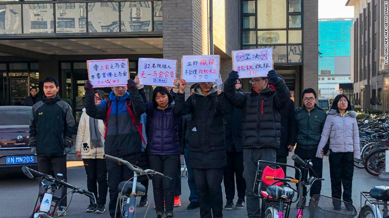A group of students hold up signs as they protest against the change in a student-run Marxist group's leadership at Peking University in Beijing on December 28, 2018.