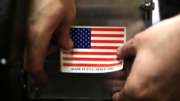 "A worker puts a ""Made in the USA"" sticker on the back of a completed lawnmower at the Dixie Chopper manufacturing facility in Coatesville, Indiana, U.S., on Friday, June 12, 2015. The U.S. Census Bureau is scheduled to release durable goods figures on June 23. Photographer: Luke Sharrett/Bloomberg via Getty Images"