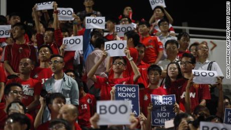 Hong Kong fans holding up signs reading