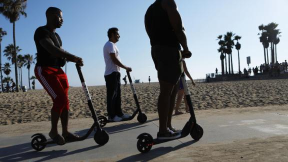 LOS ANGELES, CA - AUGUST 13:  People ride Bird shared dockless electric scooters along Venice Beach on August 13, 2018 in Los Angeles, California. Shared e-scooter startups Bird and Lime have rapidly expanded in the city. Some city residents complain the controversial e-scooters are dangerous for pedestrians and sometimes clog sidewalks. A Los Angeles Councilmember has proposed a ban on the scooters until regulations can be worked out.  (Photo by Mario Tama/Getty Images)