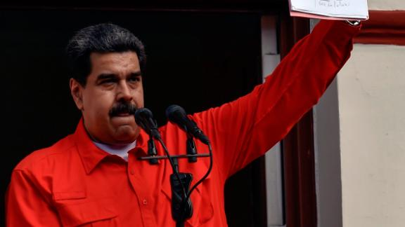 "Venezuelan President Nicolas Maduro (C) speaks to a crowd of supporters at the Miraflores Palace flanked by his wife Cilia Flores (2-L) and Vice-President Delcy Rodriguez (R), as he holds up the document with which his government broke off diplomatic ties with the United States, during a gathering in Caracas on January 23, 2019. - Venezuelan President Nicolas Maduro announced on Wednesday he was breaking off diplomatic ties with the United States after his counterpart Donald Trump acknowledged opposition leader Juan Guaido as the South American country's ""interim president."" (Photo by Luis ROBAYO / AFP)        (Photo credit should read LUIS ROBAYO/AFP/Getty Images)"