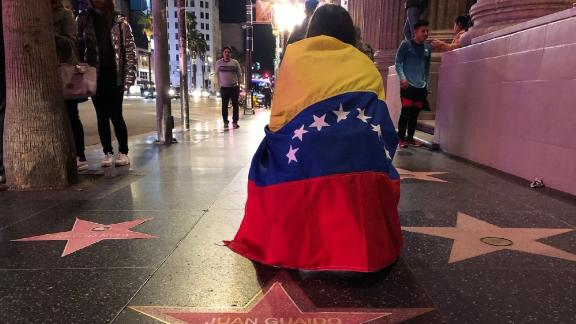 "A woman with a Venezuelan flag wrapped around her shoulders kneels behind a paper star reading ""Juan Guaido President of Venezuela"" placed on the Hollywood Walk of Fame during a demonstration held by Venezuelans in support of Guaido in Hollywood on January 23, 2019. - The United States and major South American nations recognised Venezuelan opposition leader Juan Guaido as interim leader on January 23 while the EU called for free elections to restore democracy, leaving President Nicolas Maduro increasingly isolated. (Photo by Javier TOVAR / AFP)        (Photo credit should read JAVIER TOVAR/AFP/Getty Images)"
