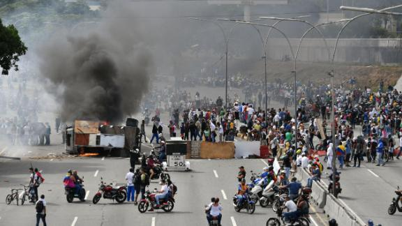 """Venezuelan opposition demonstrators set up a barricade to block a street, during a protest against the government of President Nicolas Maduro, on the anniversary of 1958 uprising that overthrew military dictatorship in Caracas on January 23, 2019. - Venezuela's National Assembly head Juan Guaido declared himself the country's """"acting president"""" on Wednesday during a mass opposition rally against leader Nicolas Maduro. (Photo by Yuri CORTEZ / AFP)        (Photo credit should read YURI CORTEZ/AFP/Getty Images)"""