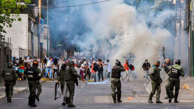 "TOPSHOT - Riot police clash with opposition demonstrators during a protest against the government of President Nicolas Maduro on the anniversary of the 1958 uprising that overthrew the military dictatorship, in Caracas on January 23, 2019. - Venezuela's National Assembly head Juan Guaido declared himself the country's ""acting president"" on Wednesday during a mass opposition rally against leader Nicolas Maduro. (Photo by YURI CORTEZ / AFP)        (Photo credit should read YURI CORTEZ/AFP/Getty Images)"