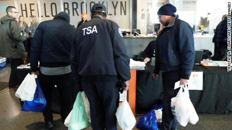 Furloughed Transportation Security Administration (TSA) employees and others leave the Barclays Center with bags of food as the Food Bank For NYC holds food distribution for federal workers impacted by the government shutdown in Brooklyn, New York January 22, 2019. (Photo by TIMOTHY A. CLARY / AFP)        (Photo credit should read TIMOTHY A. CLARY/AFP/Getty Images)