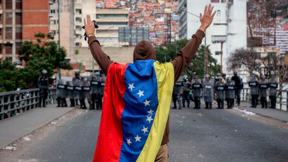 A man wrapped in a Venezuelan flag raises his arms in front of security forces during anti-government protests in Caracas on Wednesday, January 23.