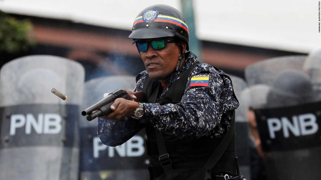 A National Police officer fires rubber bullets in Caracas.