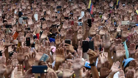 People raise their hands to show solidarity with Guaido, who was declaring himself interim president on January 23.