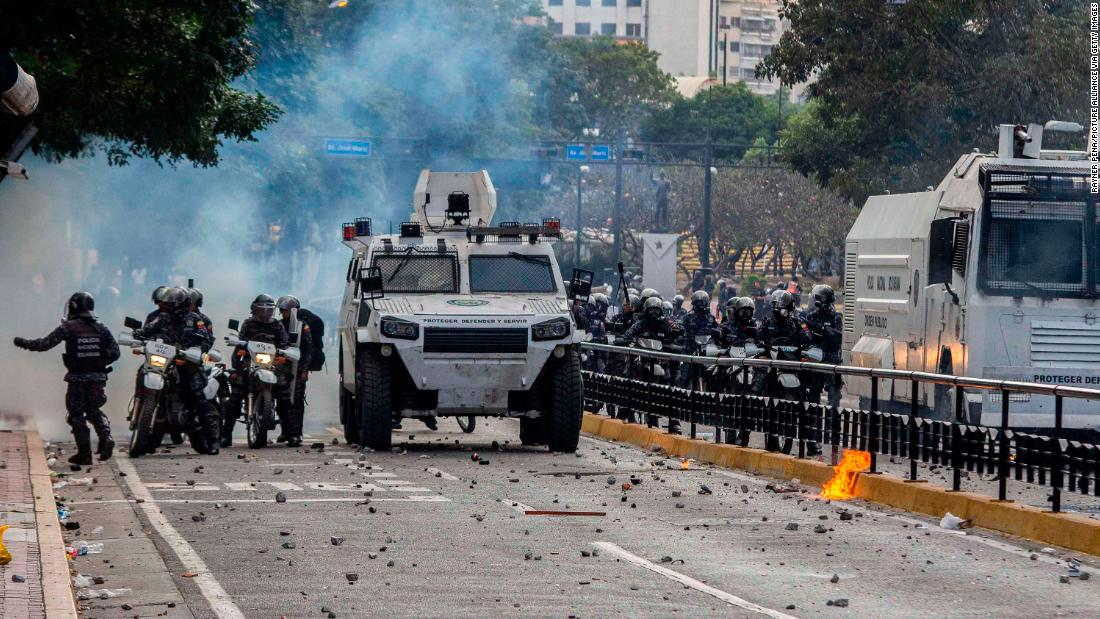 Security forces stand in a street full of stones after clashing with demonstrators in Caracas.