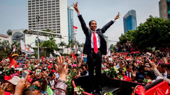 Jokowi waves to the crowd while on his journey to Presidential Palace following his election in October 2014.