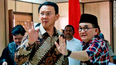 "Jakarta Governor Basuki Tjahaja Purnama, popularly known as ""Ahok"" (left) and his campaign spokesman Ruhut Sitompul (right) wave to photographers after his trial for blasphemy at the North Jakarta District Court in Jakarta on December 13, 2016."