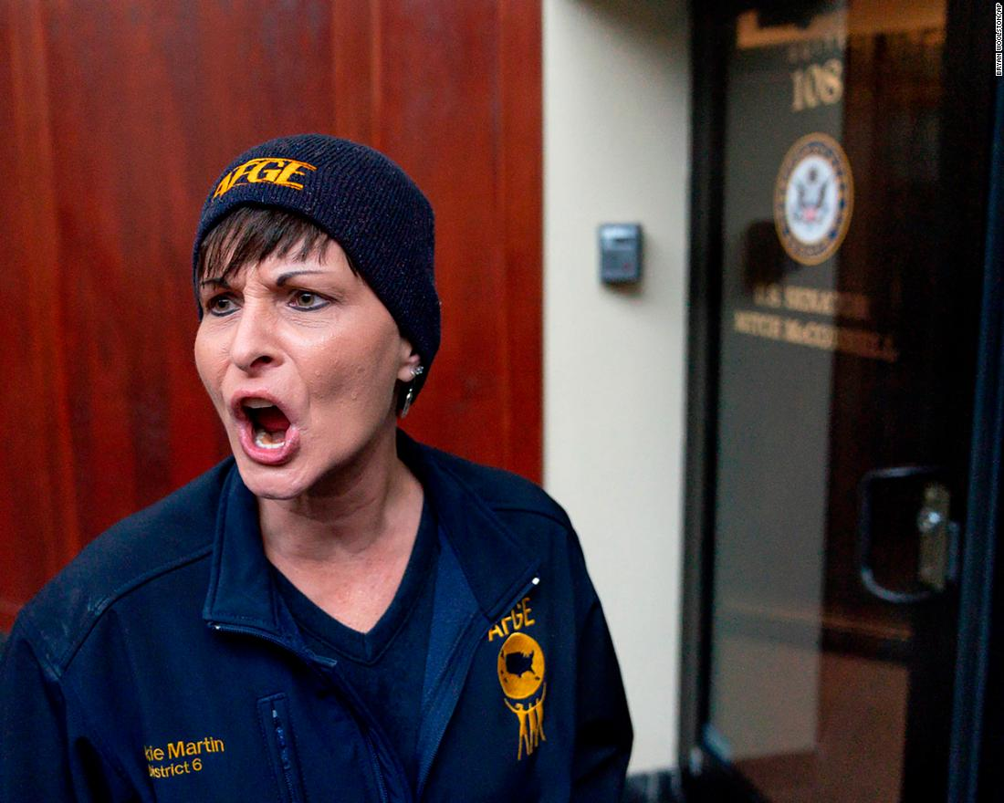 Vickie Martin, president of the American Federation of Government Workers Local 1438, reacts to the locked door of US Sen. Mitch McConnell's office in Lexington, Kentucky, during a January 23 protest.