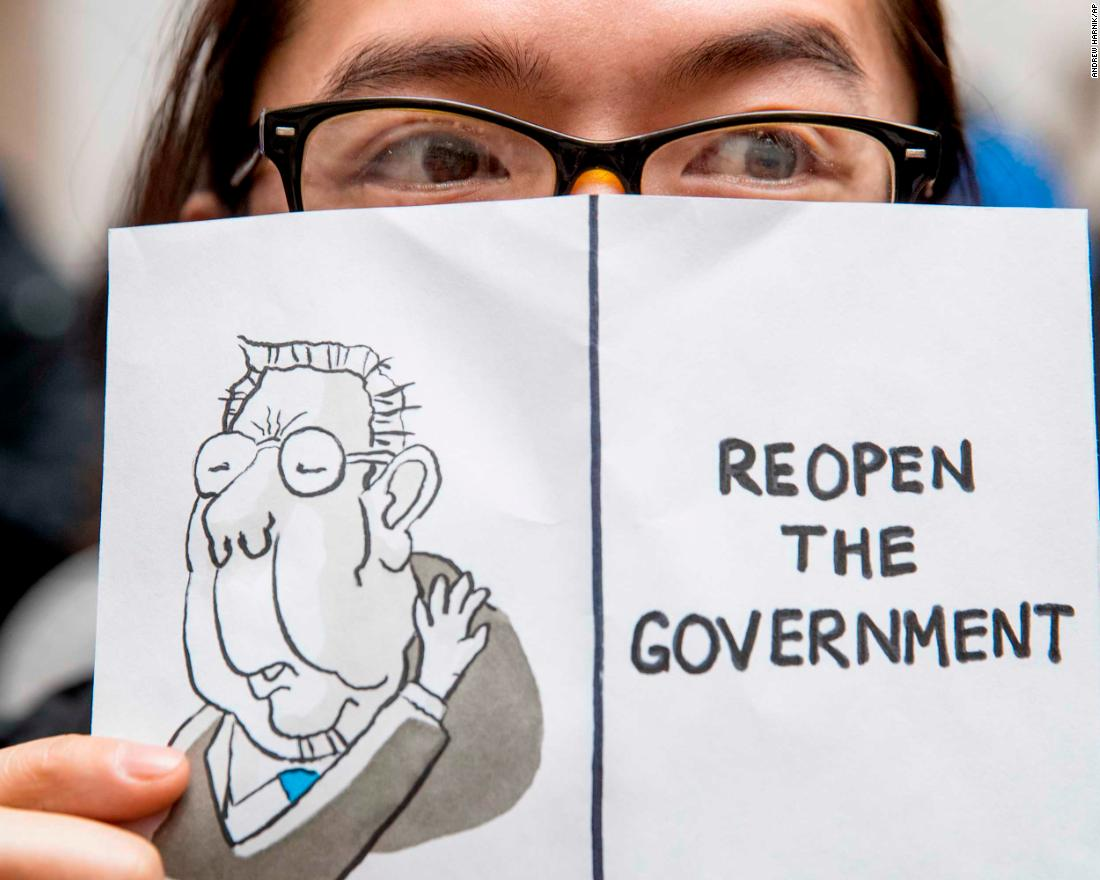 "A furloughed worker displays a sign that reads ""Reopen the Government"" during a protest in Washington on January 23."