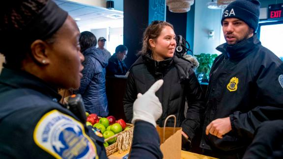 Metropolitan Police Officer and volunteer Adriane Benson, left, takes a food order for Shane Smith, a TSA agent, right, as he and other furloughed government workers affected by the shutdown receive free food and supplies at World Central Kitchen, the not-for-profit organization started by Chef Jose Andres, Tuesday, Jan. 22, 2019 in Washington. The organization devoted to providing meals in the wake of natural disasters, has set up a distribution center just blocks from the U.S. Capitol building to assist those affected by the government shutdown. (AP Photo/Andrew Harnik)
