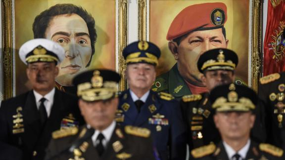 Portraits of former Venezuelan leaders Simon Bolivar and Hugo Chavez hover in the background as Venezuelan Defense Minister Vladimir Padrino Lopez, bottom left, addresses a news conference in Caracas on Thursday, January 24. Venezuela