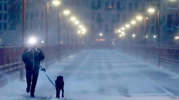 A runner and his dog brave frigid conditions while making their way east across the Stone Arch Bridge, Thursday, Jan. 24, 2019, in Minneapolis.