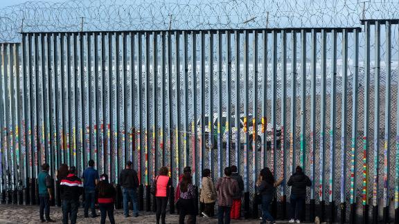 People look at US border patrol guards through the US-Mexico border fence, in Tijuana, in Baja California State, Mexico, on January 18, 2019. - A new caravan of Central American migrants trying to reach the United States made its way across Guatemala Thursday, with the first members crossing into southern Mexico. (Photo by Guillermo Arias / AFP)        (Photo credit should read GUILLERMO ARIAS/AFP/Getty Images)