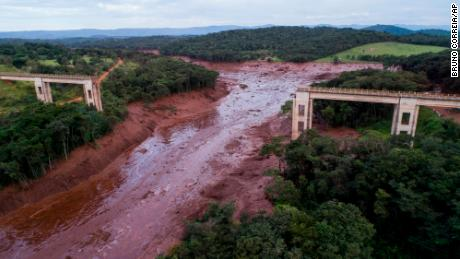 An aerial view shows a collapsed bridge flooded by a broken dam on Friday in southeastern Brazil